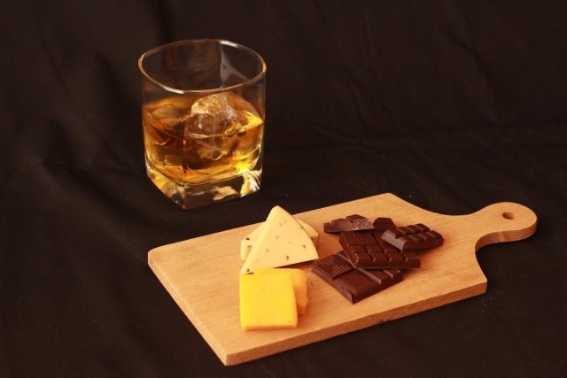 ウイスキーのロックとまな板の上にチーズと板チョコが乗っている