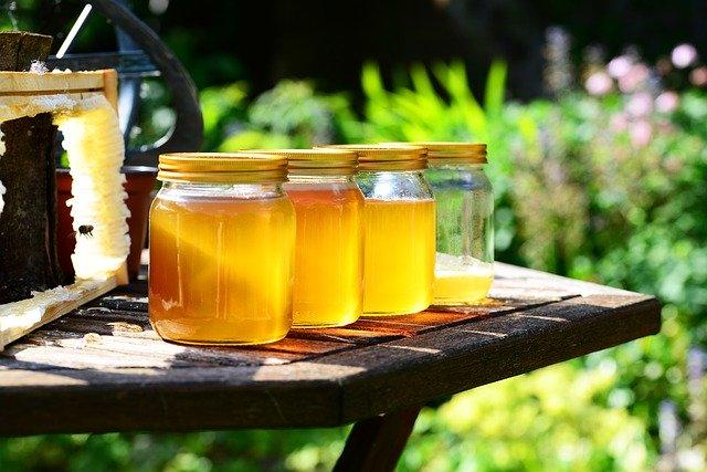 屋外のテーブルの上に4つ瓶詰されたハチミツがある
