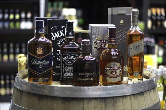 樽の上にたくさんのウイスキーの瓶が乗っている ジャックダニエル、バレンタイン、シーバスリーガル等