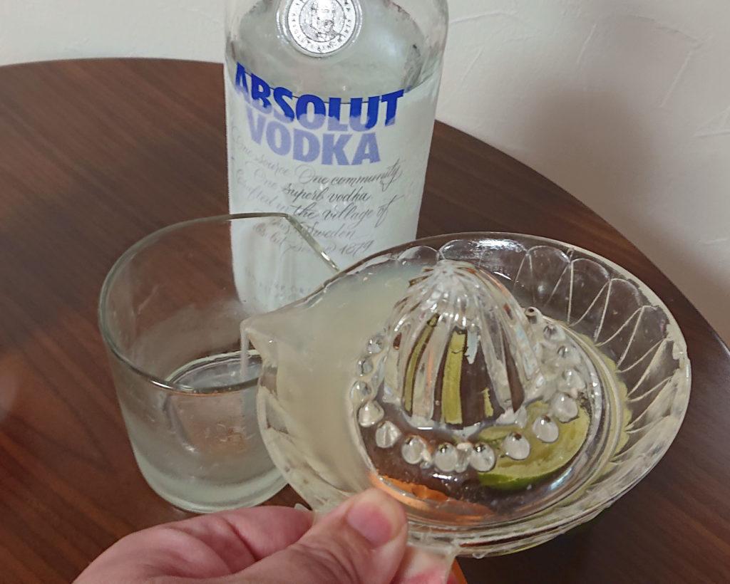 空のグラスに絞ったライムジュースを注ぐ