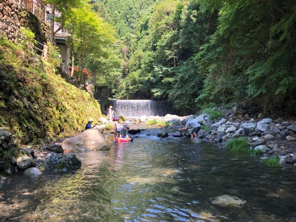 穏やかな川で川遊びをしている様子 周りは森林になており、奥にはちょっとした滝がある