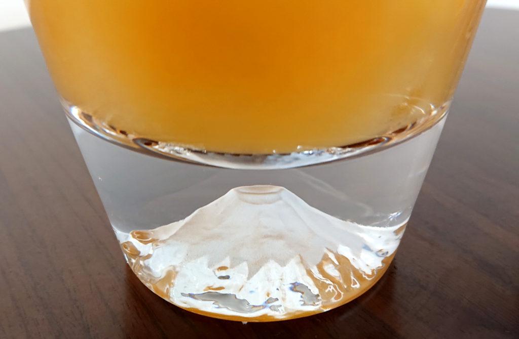 富士山ロックグラスにオレンジジュースを入れたことにより、富士山のふもとがオレンジ色に