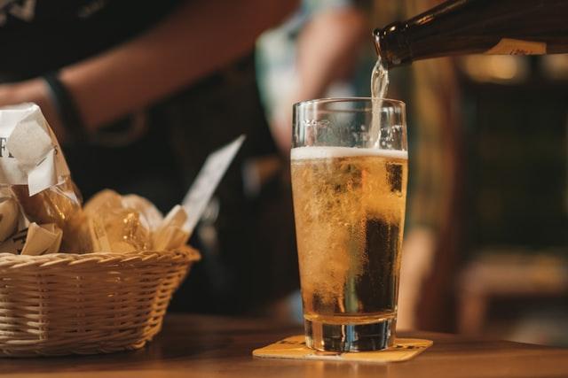 ビール瓶からビールを注いでいる パンのバケットもある