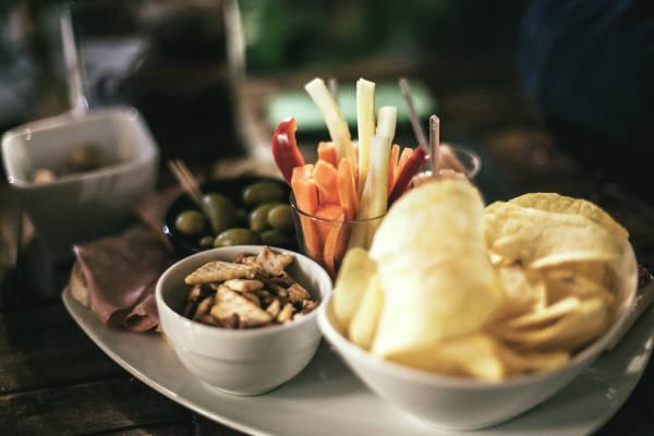 野菜スティック、ポテトチップス、クラッカー、オリーブなどのおつまみ