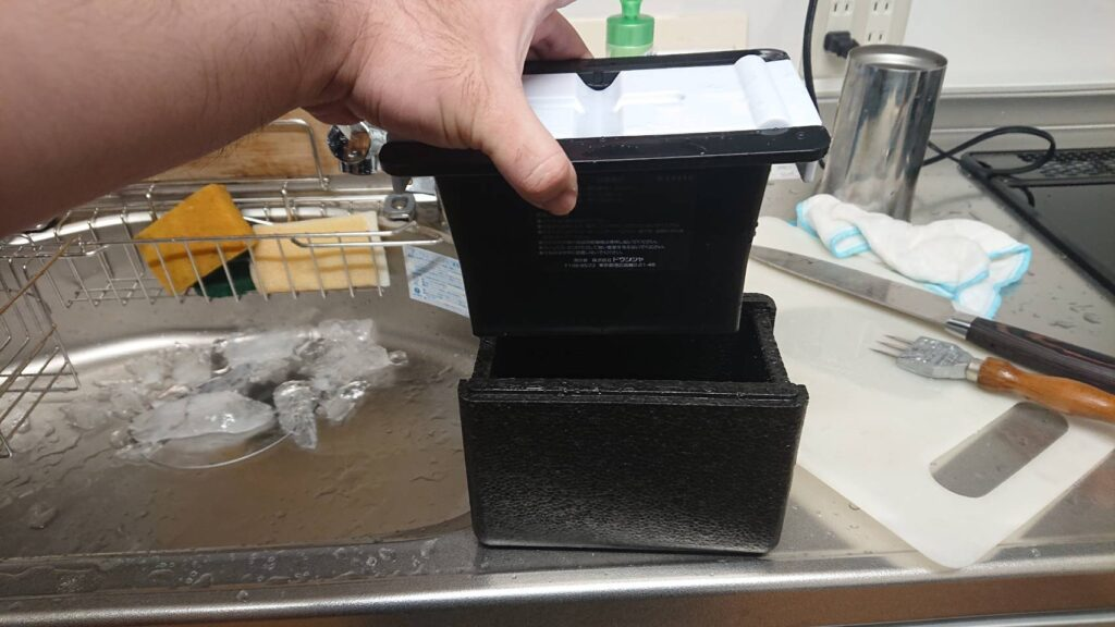 ドウシシャのクリアアイスボール製氷機の黒いボックスをゆっくり発泡スチロールに入れる様子